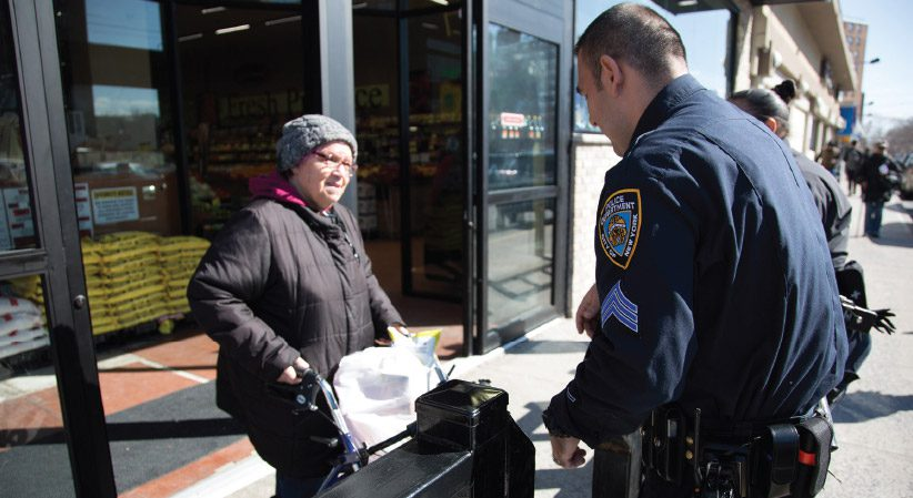 Sergeant Adolfo Enciso '19 assisting a woman in the Bronx.