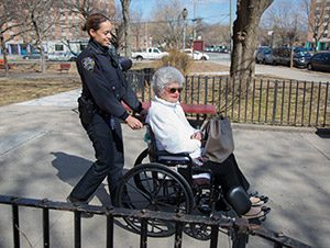 police officer pushing an elderly woman in wheelchair